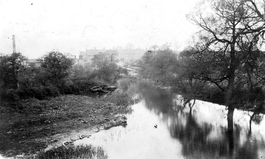 The River Anker at Polesworth, with the old brick works on the left. Note the two cart wheels half submerged in the foreground.  1910s    IMAGE LOCATION: (Warwickshire County Record Office)