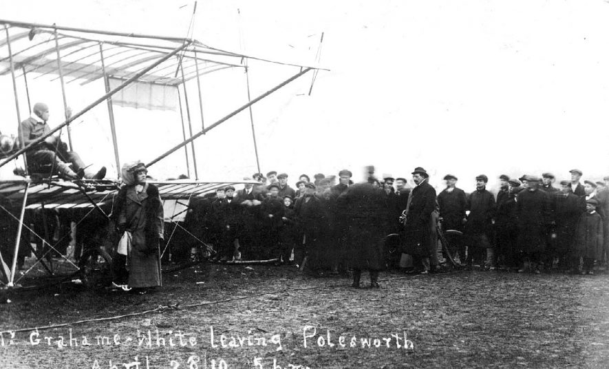 Photograph bears the inscription: Mr Grahame White leaving Polesworth, April 28th 1910 at 5 p.m.  It shows the incredible flying machine he flew, and a large number of interested onlookers |  IMAGE LOCATION: (Warwickshire County Record Office) PEOPLE IN PHOTO: White, Grahame, White as a surname