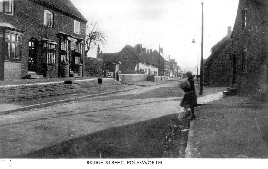 Street scene in Polesworth showing the elevated pavement.  The building on the left has an unusual double bow fronted window.  1920s |  IMAGE LOCATION: (Warwickshire County Record Office)