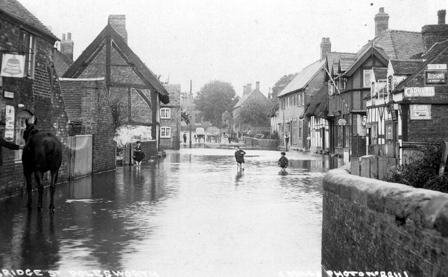 Floods in Bridge Street, Polesworth, in the 1910s. The horse is standing outside the Telegraph Office with the sign of the bell sporting the logo 'National Telephone Service.  On the right there is a barber's pole over the sign which reads 'Haircutting, shaving and shampooing rooms' |  IMAGE LOCATION: (Warwickshire County Record Office)