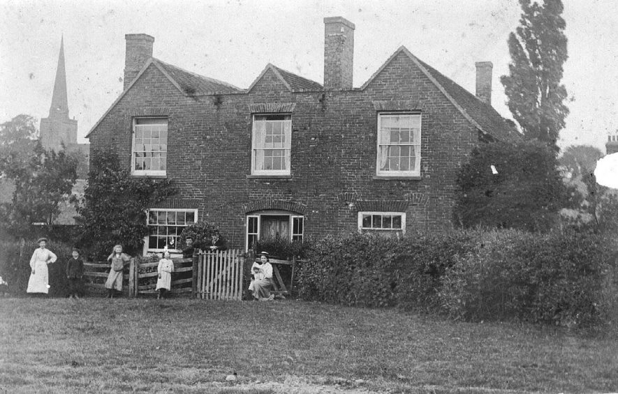 A farmhouse near Seckington parish church. Members of family outside front gate.  1900s |  IMAGE LOCATION: (Warwickshire County Record Office)