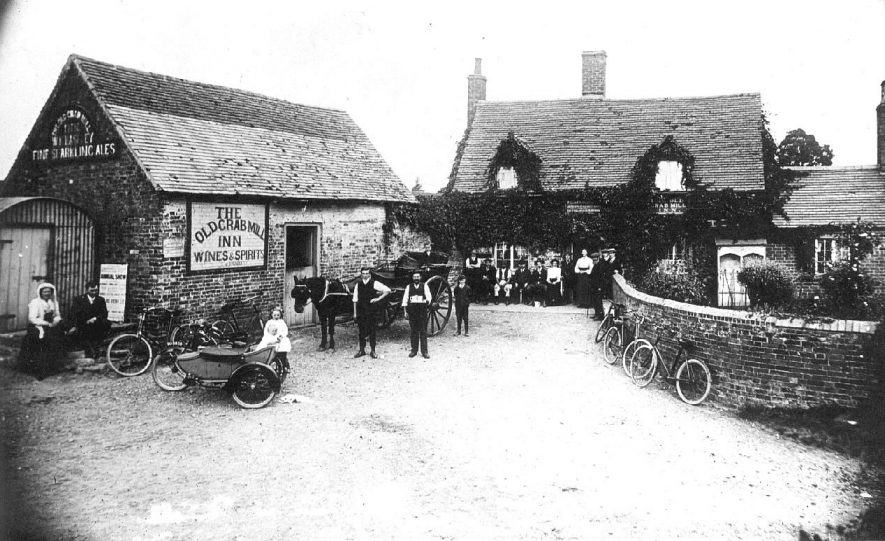 The Old Crab Mill Inn (prop. William King Baseley) with many people outside, Preston Bagot. Several examples of bicycles, a pony and trap and a motor-cycle with side-car.  1910s. |  IMAGE LOCATION: (Warwickshire County Record Office)