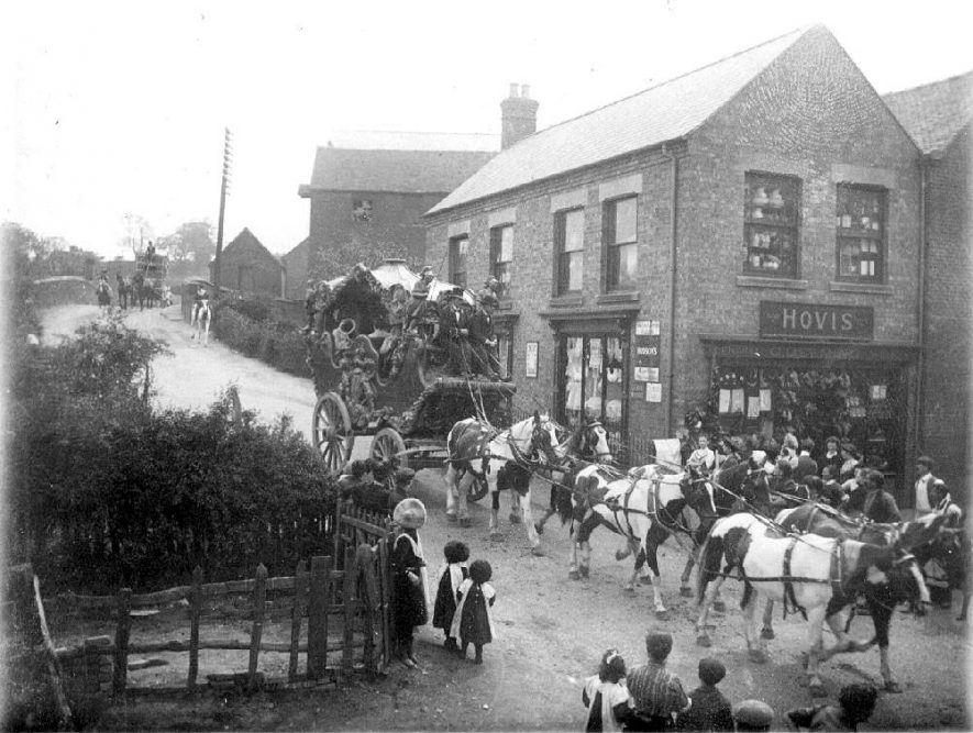 Large decorated coach and six, passing along Market Street, Polesworth in front of Randles general grocers.  The coachman is resplendent in his livery complete with top hat.  The side window of the stores has a display of haberdashery.  1900s |  IMAGE LOCATION: (Warwickshire County Record Office)