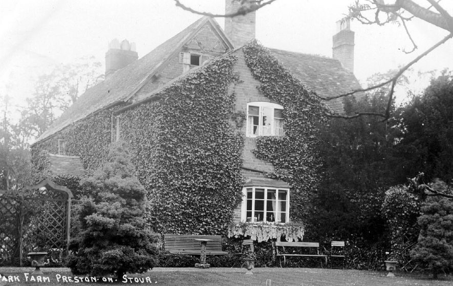 Large farmhouse with attractive garden furnishing including on ogee shaped arbour and a rustic window box covered with bark.  1900s |  IMAGE LOCATION: (Warwickshire County Record Office)