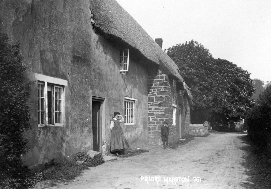 A girl and a boy standing outside a thatched cottage, Priors Marston.  1900s |  IMAGE LOCATION: (Warwickshire County Record Office)