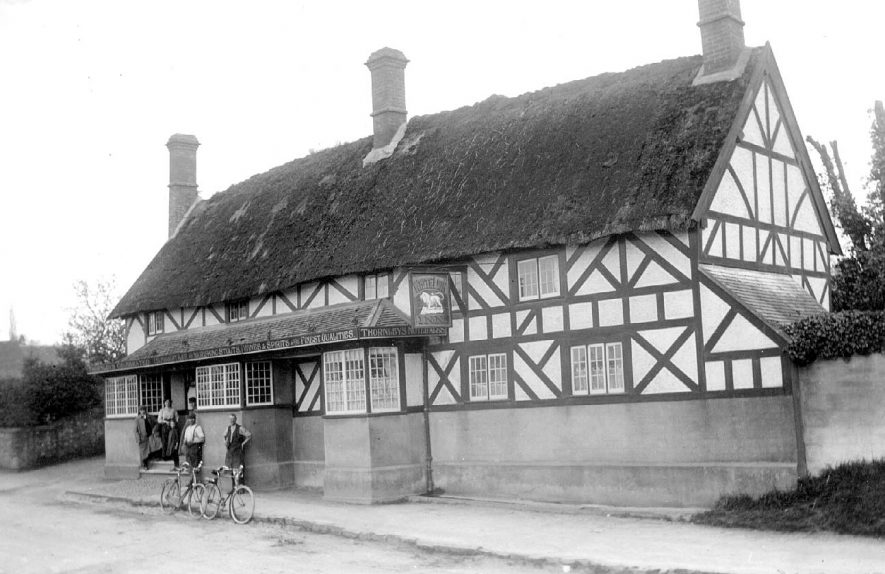 Group of people with two bicycles standing outside The White Lion Inn, Radford Semele.  1920s |  IMAGE LOCATION: (Warwickshire County Record Office)