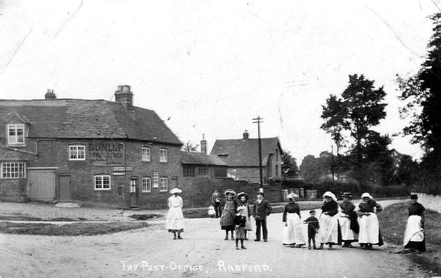Group of women and children standing in the road with the Post Office, Radford Semele, in the background.  1900s |  IMAGE LOCATION: (Warwickshire County Record Office)