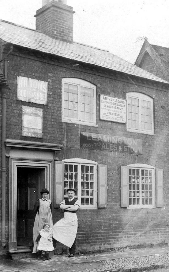 Man, woman and child standing at the entrance of Arthur Adams, licensed retailer's shop. Rows of sweet jars standing in windows. Radford Semele.  1900s |  IMAGE LOCATION: (Warwickshire County Record Office)