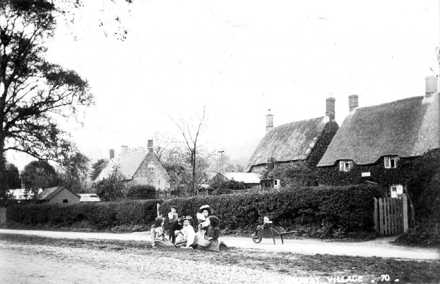 Children sitting on grass verge in front of cottages in Radway. Wheelbarrow.  1900s    IMAGE LOCATION: (Warwickshire County Record Office)