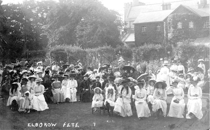 Large group of people in the grounds of the rectory at Elborow Fete, Rugby.  1910s [A young girl in the front row to the right of the word