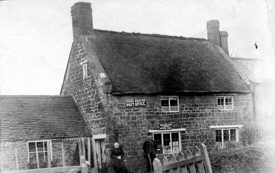 Post office with an old lady and a postman outside, Priors Marston.  1900s |  IMAGE LOCATION: (Warwickshire County Record Office)