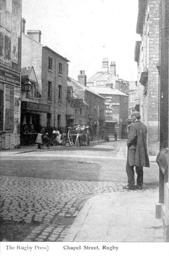 Street with horses and carriages and hand cart, Rugby.  1900s