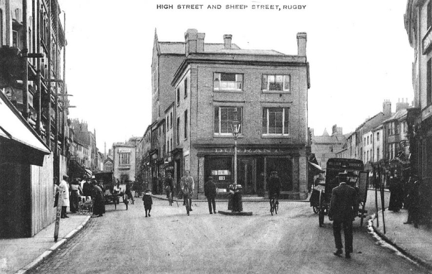 Market Place looking into High Street and Sheep Street, Rugby. Showing delivery van, bicycles and people shopping. 1910s |  IMAGE LOCATION: (Warwickshire County Record Office)