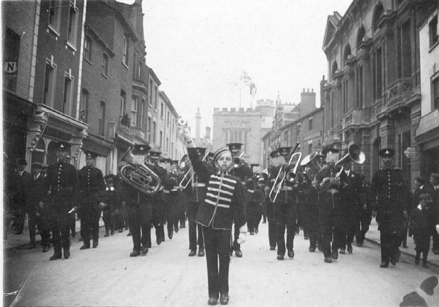 Brass band marching along High Street, Rugby.  1900s |  IMAGE LOCATION: (Warwickshire County Record Office)