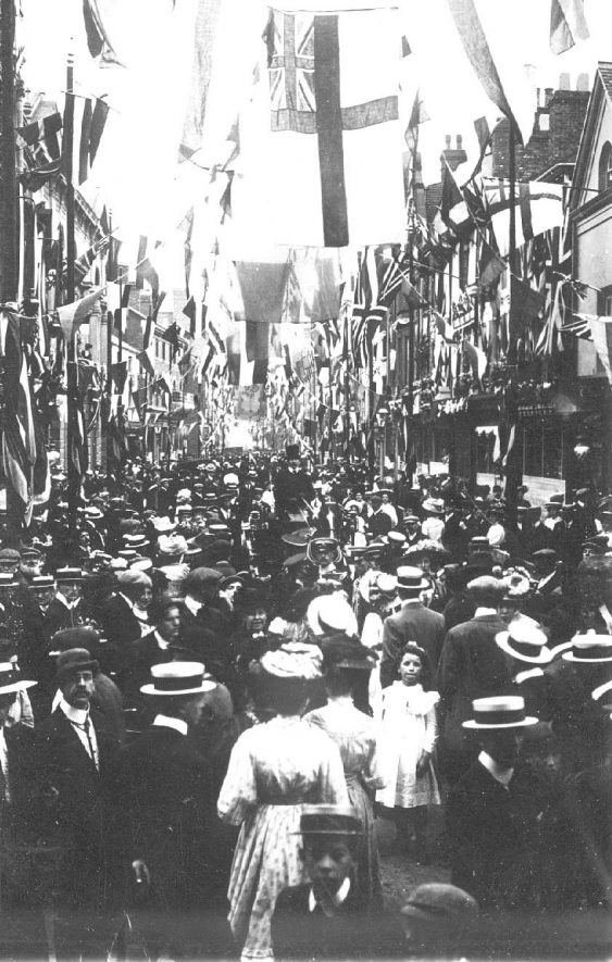 Crowds in highly decorated Rugby street for royal visit 1909. |  IMAGE LOCATION: (Warwickshire County Record Office)
