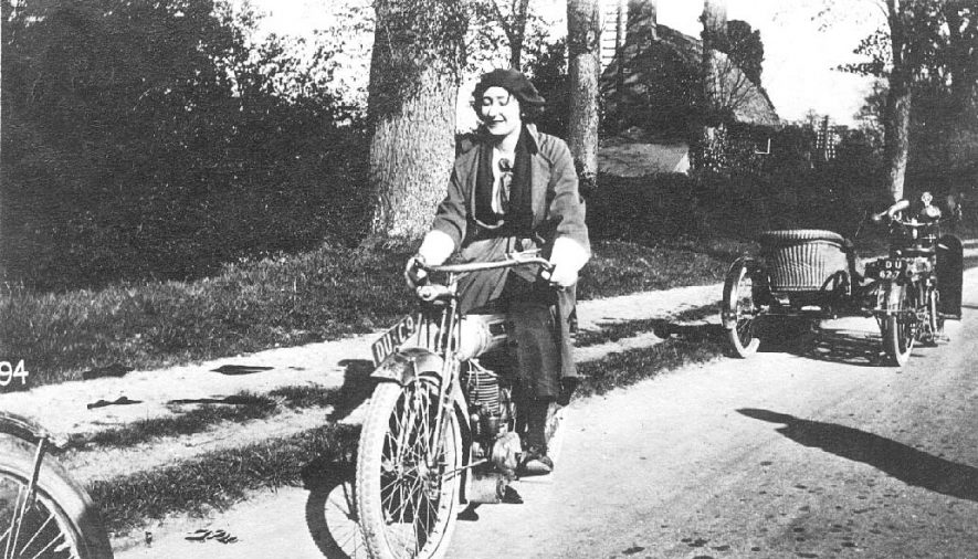 Motorcycles, one being ridden by a lady.  Captioned