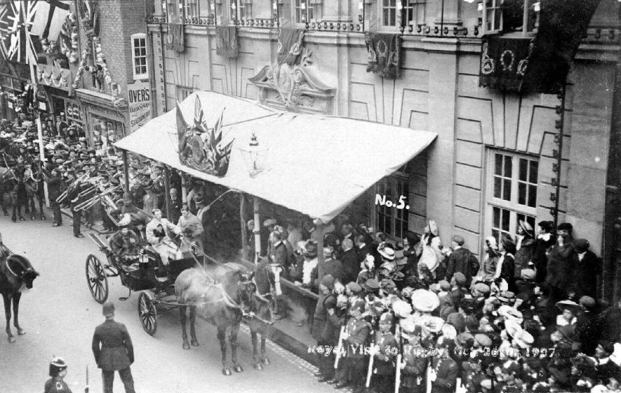 Horses and carriages, one containing royal lady or ladies, policemen, brass band and onlookers at the royal visit, Rugby.  1907 |  IMAGE LOCATION: (Warwickshire County Record Office)