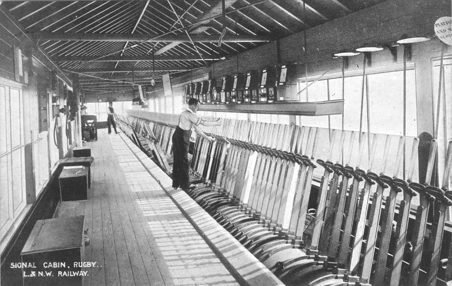 Interior of London & North Western Railway signal box, Rugby, with two signalmen at work.  Printed at back :