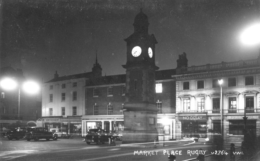 Rugby Market Place at night showing clock tower, shop fronts and parked cars.  1930s |  IMAGE LOCATION: (Warwickshire County Record Office)