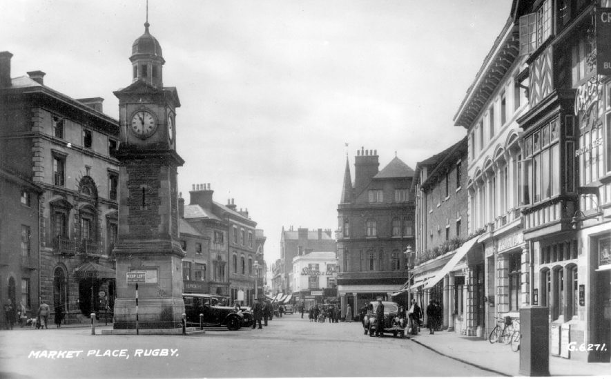 Rugby Market Place showing shops, clock tower and motor cars.  1930s |  IMAGE LOCATION: (Warwickshire County Record Office)