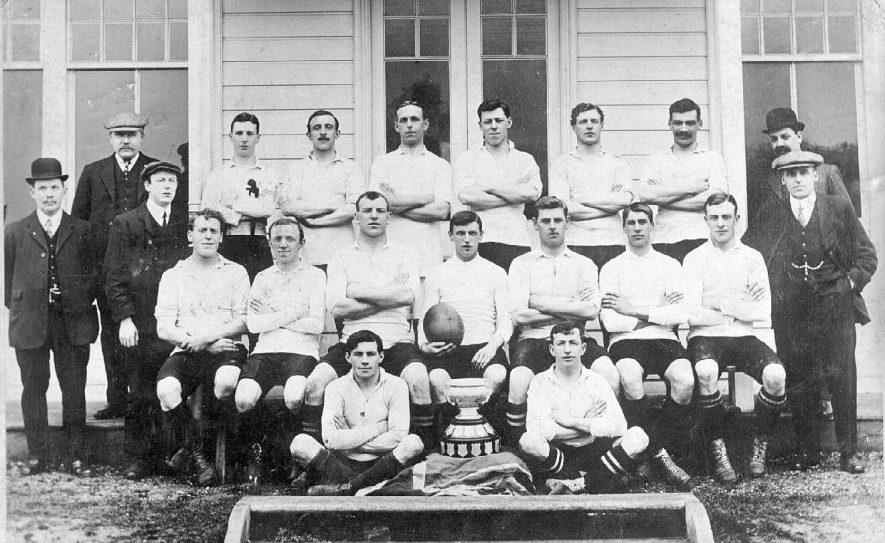 Rugby XV team photograph complete with trophy, possibly a team from Rugby.  1910s |  IMAGE LOCATION: (Warwickshire County Record Office)