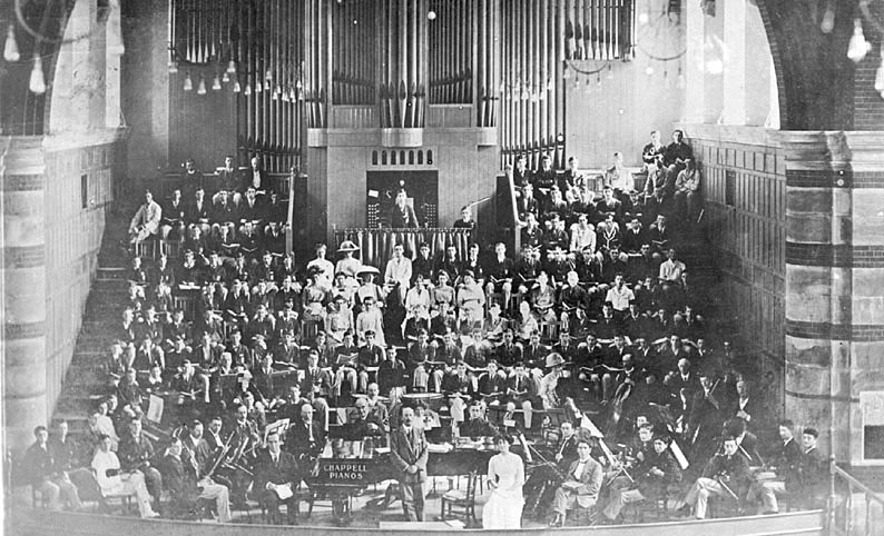 The Speech Room, Rugby School  showing the choir and orchestra.  1900s |  IMAGE LOCATION: (Warwickshire County Record Office)