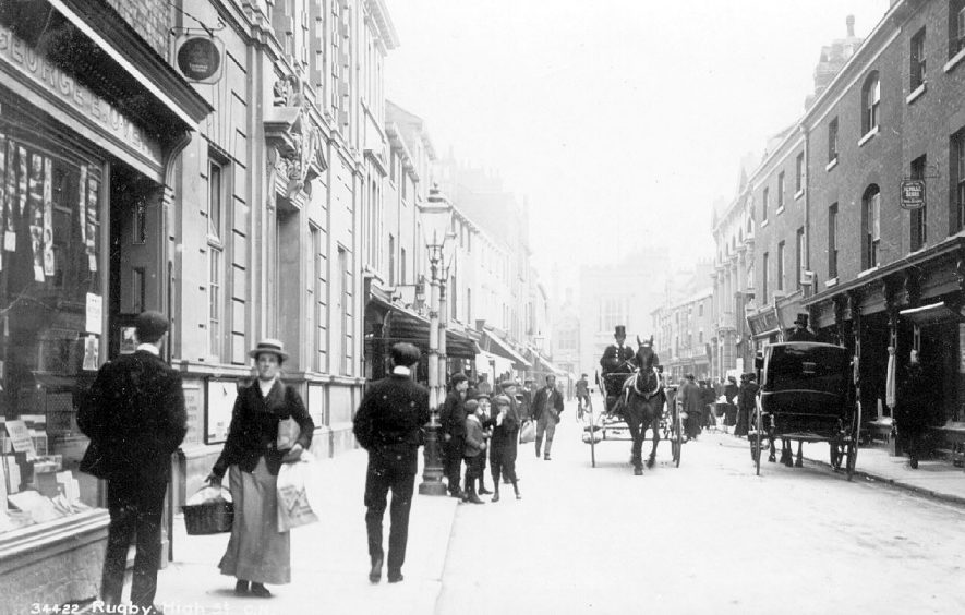 High Street, Rugby, showing horse drawn vehicles including a cab and pedestrians.  Near left of photograph is George E. Over, stationers and printers. photo no. The Photochrom Co. Ltd. 34422.  1900s |  IMAGE LOCATION: (Warwickshire County Record Office)
