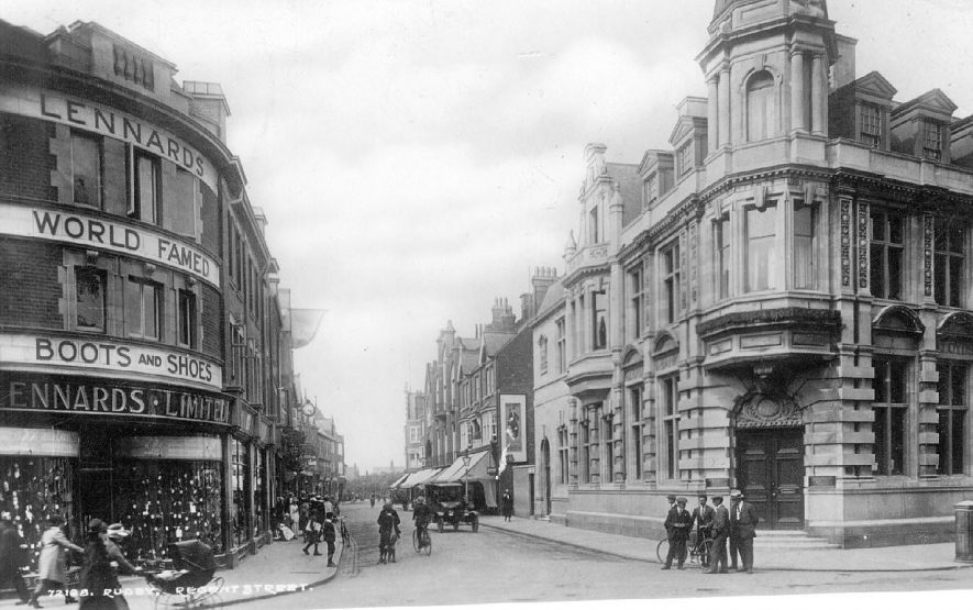 The approach to Regent Street, Rugby showing Lennard's Ltd,  boot and shoe shop, on the left hand side and Lloyds Bank on the right, pedestrians cyclists. Valentine's Series. 72128.  1910s |  IMAGE LOCATION: (Warwickshire County Record Office)