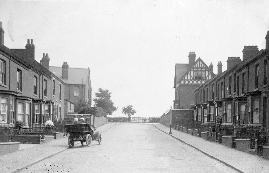 View of Winfield Road looking towards Clifton Road, Rugby showing rows of terraced houses on both sides and a motor car registration no. NH 300 half way up the street.  1900s |  IMAGE LOCATION: (Warwickshire County Record Office)