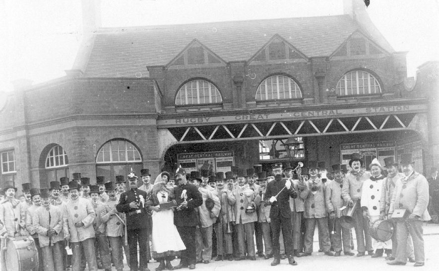Members of a band in comic/fancy dress outside Rugby Great Central Station.  1900s |  IMAGE LOCATION: (Warwickshire County Record Office)