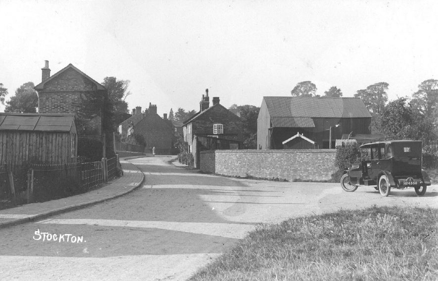 Road showing houses and farm buildings in Stockton; taxi in foreground.  1930s |  IMAGE LOCATION: (Warwickshire County Record Office)