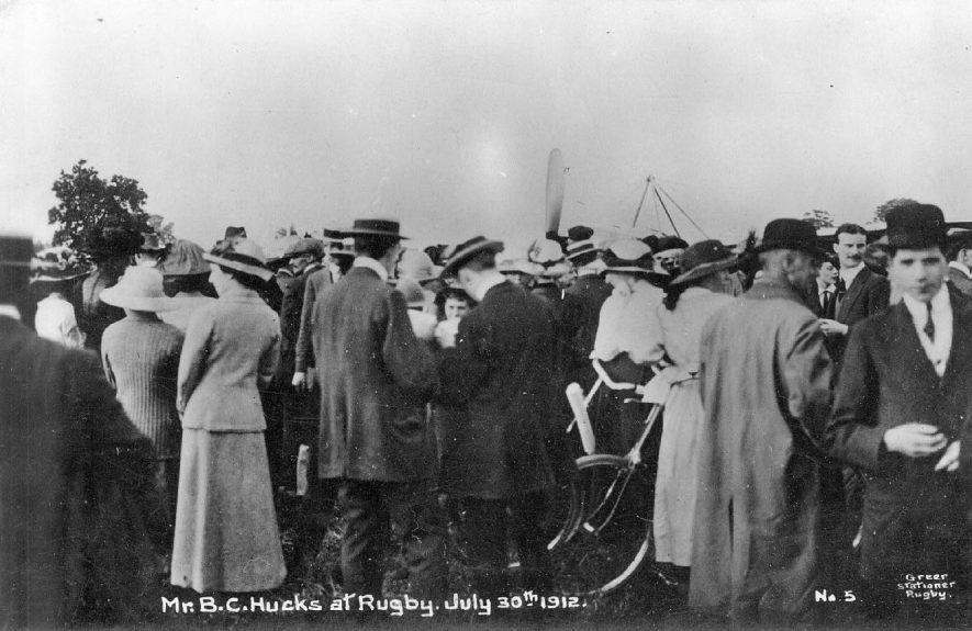 Mr B C Hucks at Rugby. His Aircraft can hardly be seen for the crowd of people.  1912 |  IMAGE LOCATION: (Warwickshire County Record Office) PEOPLE IN PHOTO: Hucks, B C, Hucks as a surname