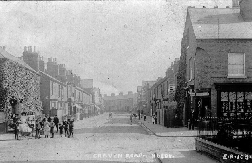 Scene from Craven Road, Rugby showing a group of children with a few women on the left and two gentlemen standing outside H. Driver, ' hairdressing and shaving' on the right. original photo. no. E.R. 108.  1900s |  IMAGE LOCATION: (Warwickshire County Record Office)