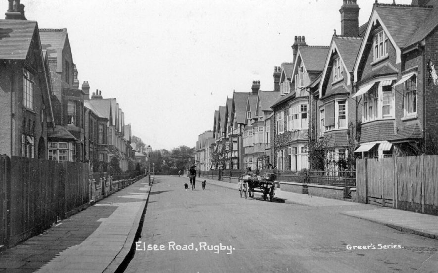 View looking down Elsee Road, Rugby showing  large terraced houses on either side, a horse and cart parked on the right hand side and two dogs in the road following a cyclist.  1900s |  IMAGE LOCATION: (Warwickshire County Record Office)