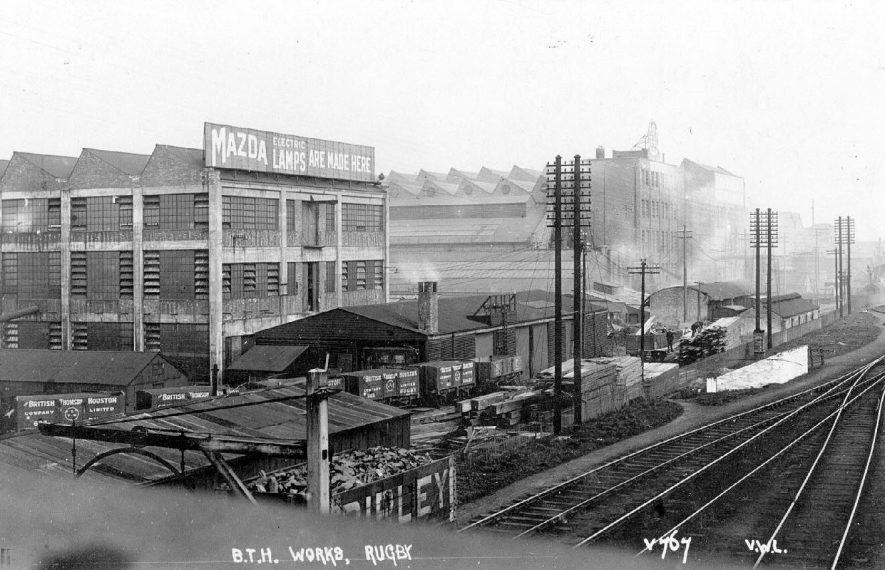 View of B.T.H. electrical engineering factory seen from the railway line, Rugby. Advertisement for Mazda Lamps on another factory building.  Goods wagons.  1930s |  IMAGE LOCATION: (Warwickshire County Record Office)