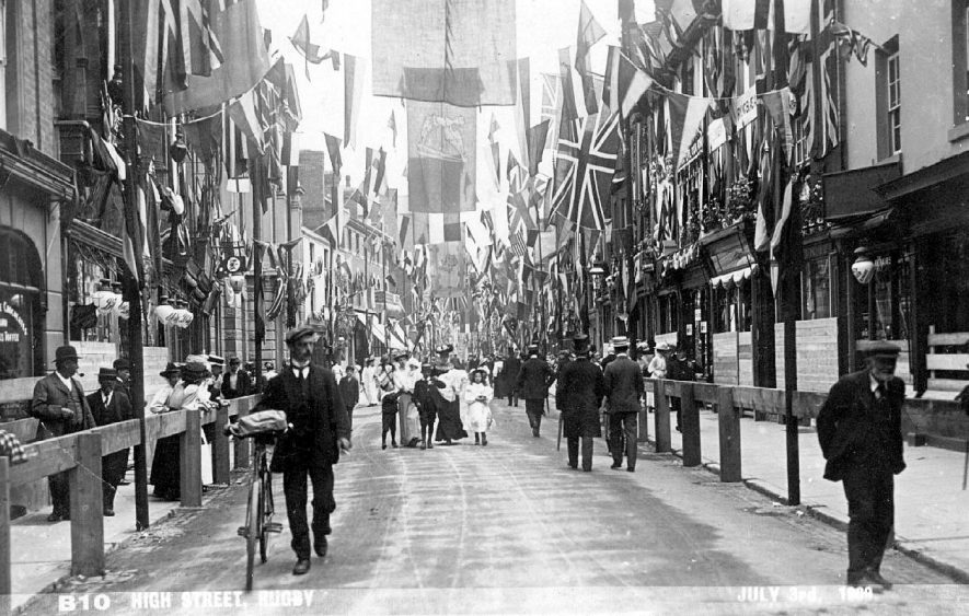 Rugby High Street decorated with flags on occasion of visit of Edward VII. Onlookers walking in street.  1909 |  IMAGE LOCATION: (Warwickshire County Record Office)