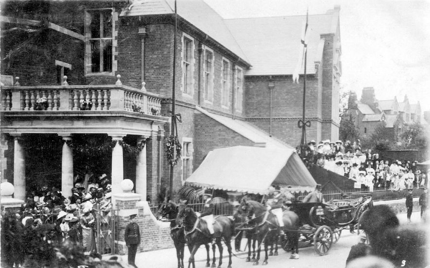 Carriage and horses outside large town building on occasion of Royal visit, Rugby.  1900s    IMAGE LOCATION: (Warwickshire County Record Office)