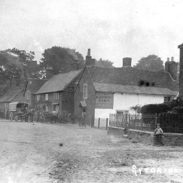 Part of village street with cottages, The Blacksmith's Arms and two storey brick house, Ryton on Dunsmore. Horse with covered cart. Children.  1900s | IMAGE LOCATION: (Warwickshire County Record Office)