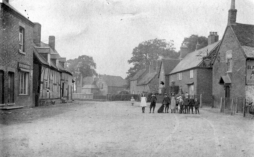 Part of village street with cottages, one timber-framed and The Blacksmith's Arms, Ryton on Dunsmore.  Group of children with dog.  1900s |  IMAGE LOCATION: (Warwickshire County Record Office)