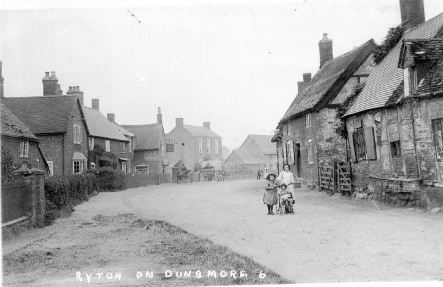 Cottages in High Street, one thatched and timber-framed. Rosy Walk and the Blacksmith's Arms are on the left.  Children with pushchair in centre of picture. Ryton on Dunsmore.  1900s |  IMAGE LOCATION: (Warwickshire County Record Office)