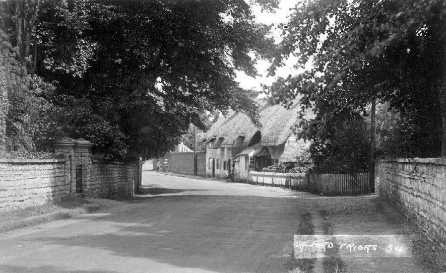 Thatched cottages lining the Evesham road at Salford Priors. Mature beech trees offer some relief from the hot summer sun for weary travellers!  1920s |  IMAGE LOCATION: (Warwickshire County Record Office)