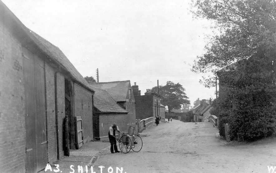 Street scene in Shilton, showing a milkman with his churns on a hand cart.  1910s |  IMAGE LOCATION: (Warwickshire County Record Office)