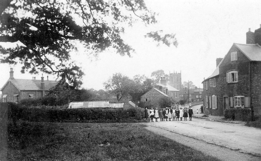 Group of schoolchildren standing in the street, with the church and the railway bridge in the background.  1900s |  IMAGE LOCATION: (Warwickshire County Record Office)