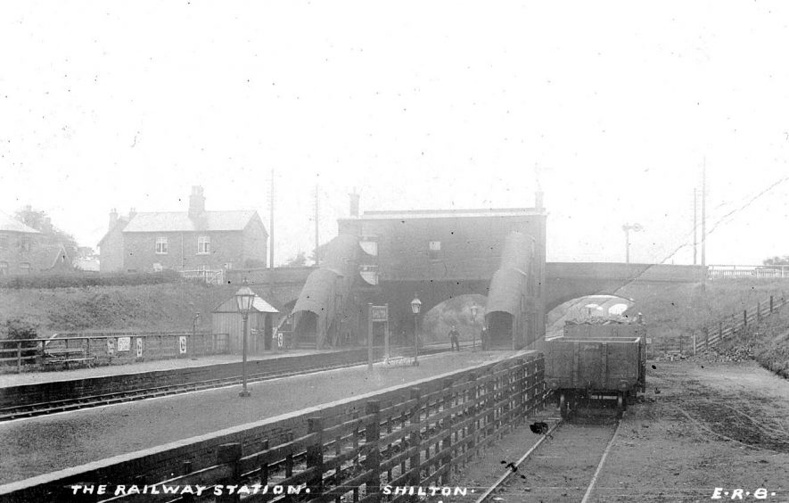 Trucks on the siding at Shilton station, showing the passenger footbridge, and the double span bridge behind.  1920s |  IMAGE LOCATION: (Warwickshire County Record Office)