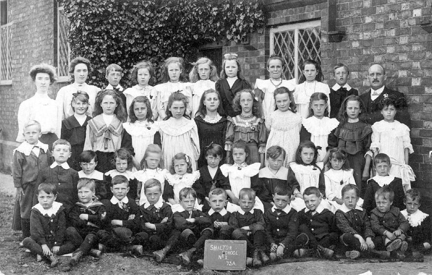 Shilton schoolchildren and their teachers.  The board reads Shilton school No 11   73A.  1900s |  IMAGE LOCATION: (Warwickshire County Record Office)
