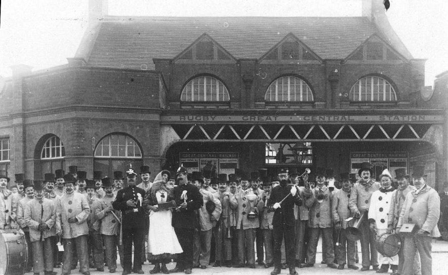 A Band in fancy dress outside the central Rugby Station.  1900s    IMAGE LOCATION: (Warwickshire County Record Office)