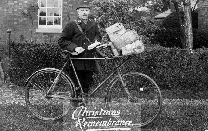 'Christmas Remembrance', postman with letters and parcels on his bicycle.  1920s |  IMAGE LOCATION: (Warwickshire County Record Office)