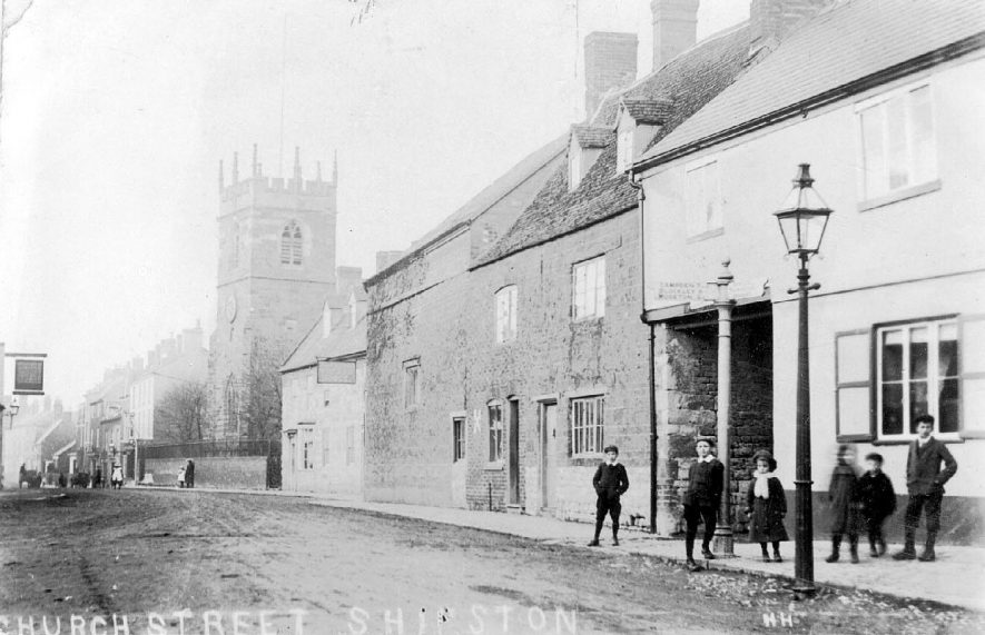 Group of children standing in Church Street, with church in the background. Shipston on Stour.  1900s |  IMAGE LOCATION: (Warwickshire County Record Office)