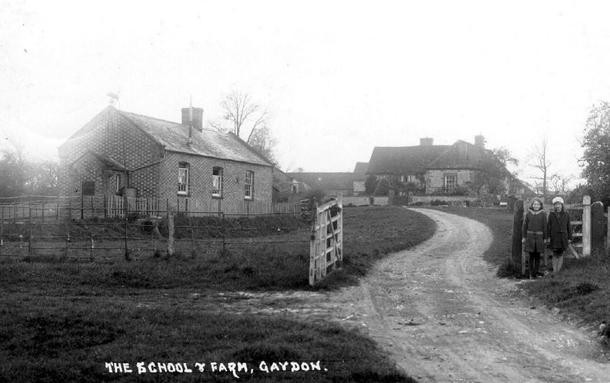 View along a rough road to the 'School and Manor Farm, Gaydon. 1930s[The girl on the right is Vera Hill who was born in 1921. She was on her way home from school with her friend ?Elsie when this photograph was taken] |  IMAGE LOCATION: (Warwickshire County Record Office)