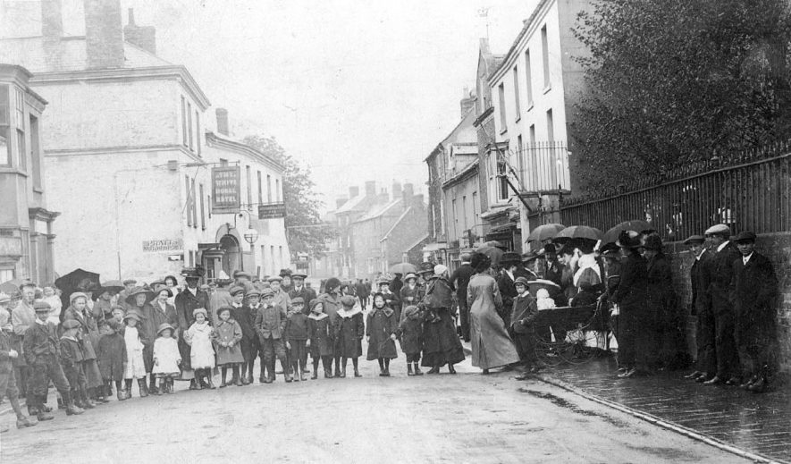 Group of children and adults posing across street for photograph. Clearly pouring with rain and blowing a gale! Possibly school or Sunday School outing. The White Horse Hotel behind them.  1900s |  IMAGE LOCATION: (Warwickshire County Record Office)